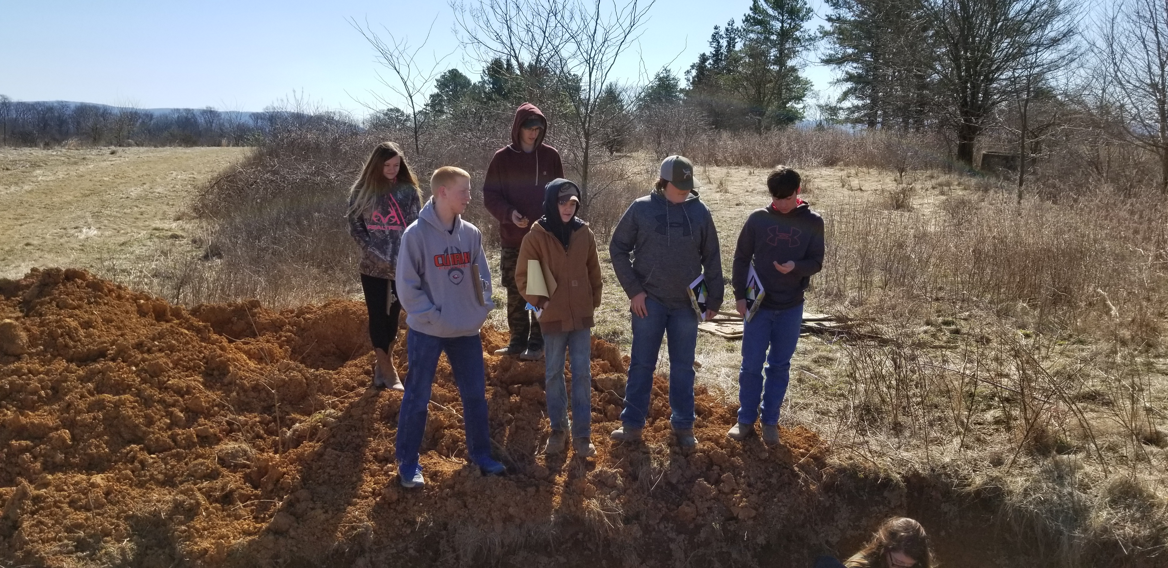 High school students gaze into a soil profile