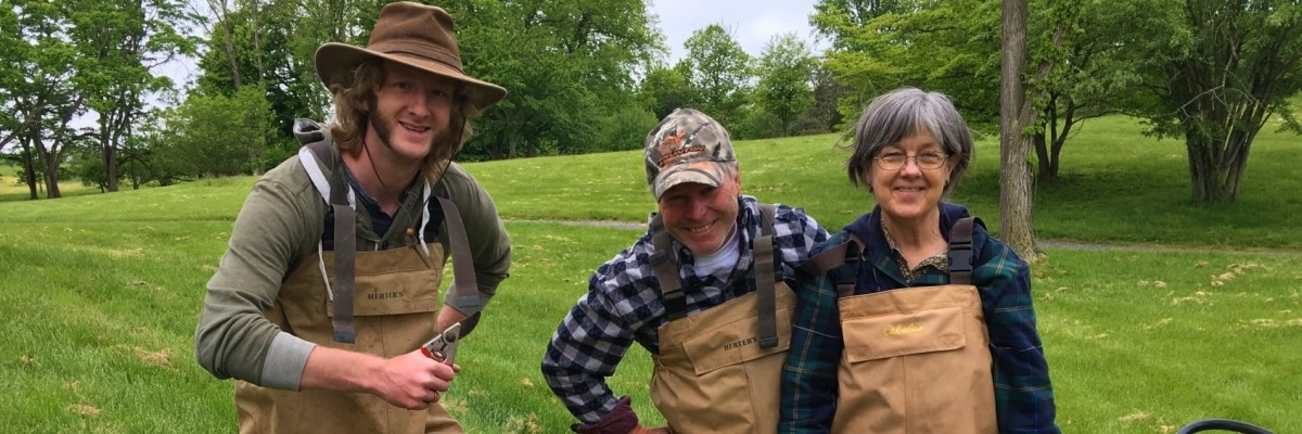Three volunteers pose wearing waders in front of a grassy hill